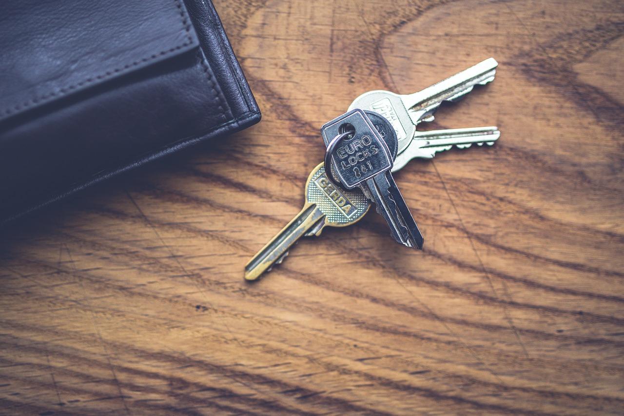 Et nøkkelknippe som ligger på et bord ved siden av en lommebok