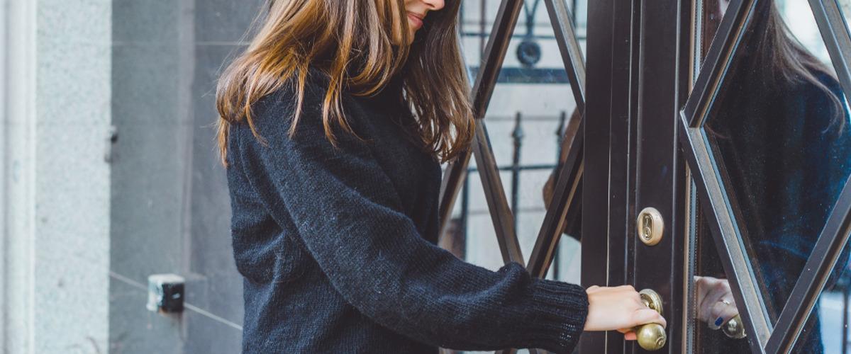 En dame som åpner opp en dør
