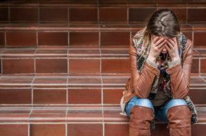En dame som sitter i en trapp med ansiktet i hendene