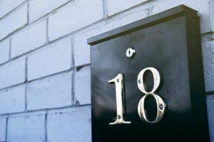 Nærbilde av en sort postkasse med tallet 18