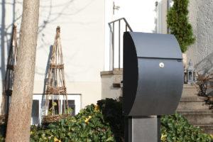 En sort postkasse med lås utenfor et hus