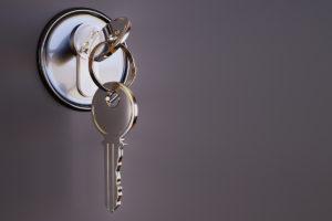 En blank nøkkel i sølv som står i en blank lås i sølv