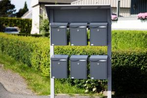 En sort postkassestativ med seks sorte postkasser