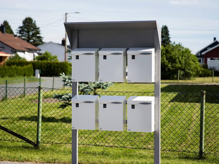 Et postkassestativ med tak og seks postkasser