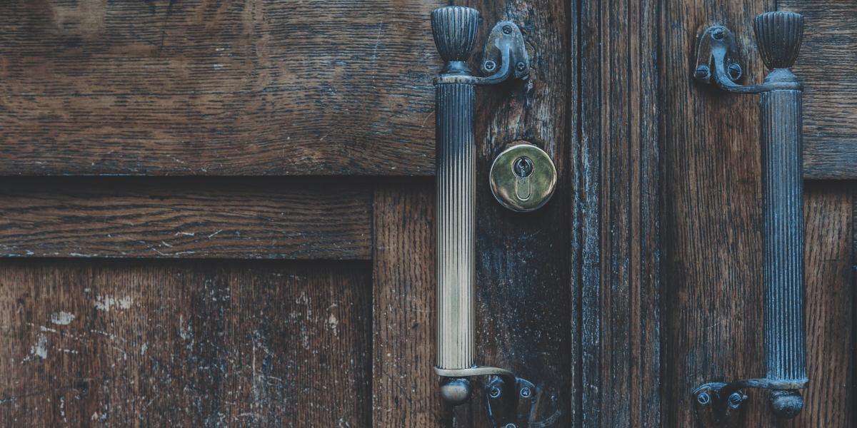 En gammel dør med lås og to håndtak