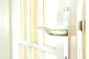 Nærbilde av håndtaket til en dør med glasspanel