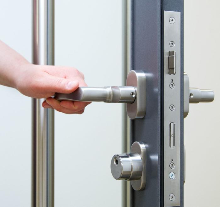 Nærbilde av en hånd som åpner en dør med adgangskontroll