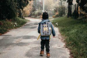 En liten gutt sett bakfra med sekk som går på en asfaltert gangvei