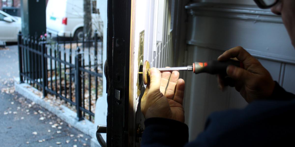 Nærbilde av en låsesmed som skrur opp låsen på en inngangsdør