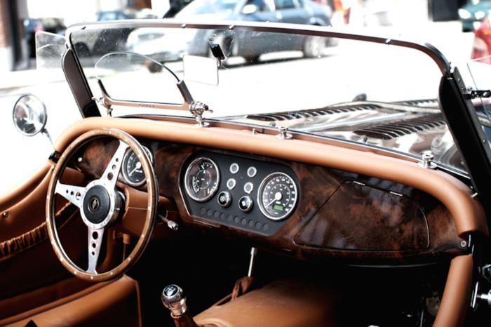 Innsiden av en veteranbil med brunt skinn-interiør sett bakfra fra siden