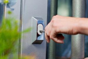 Nærbilde av en hånd som bruker en nøkkel til å låse opp en lås fra iLOQ