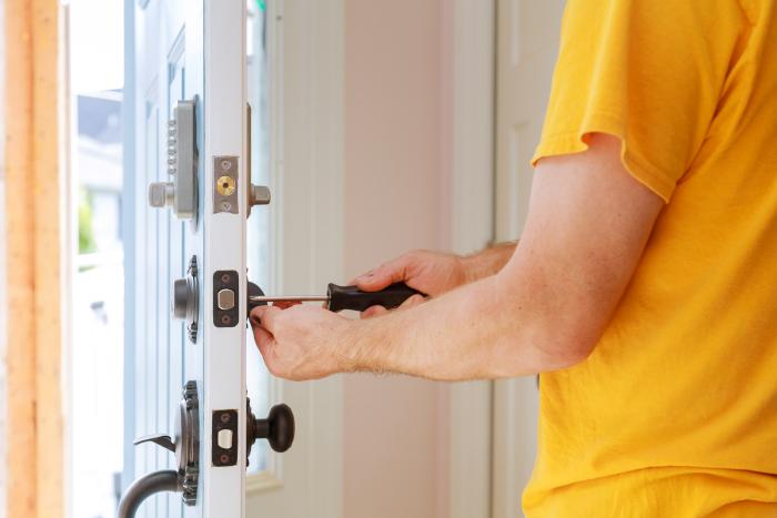 En mann som skrur opp låsen på en åpen dør