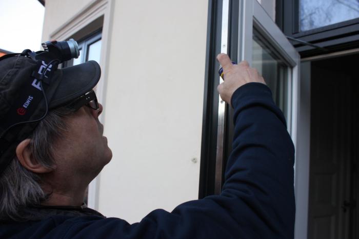 En låsesmed som smører en verandadør
