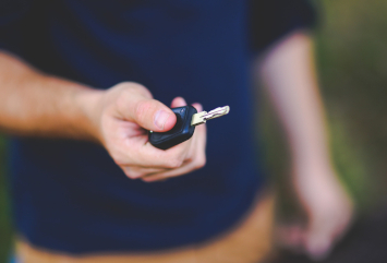 Nærbilde av hånden til en mann som holder en bilnøkkel