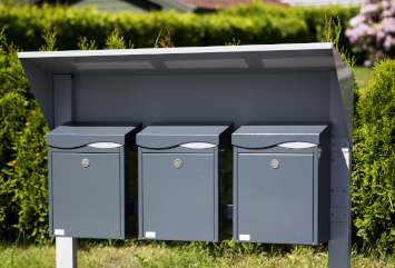 Et postkassestativ med tre postkasser i sort