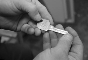 Nærbilde av en nøkkel som holdes i to hender