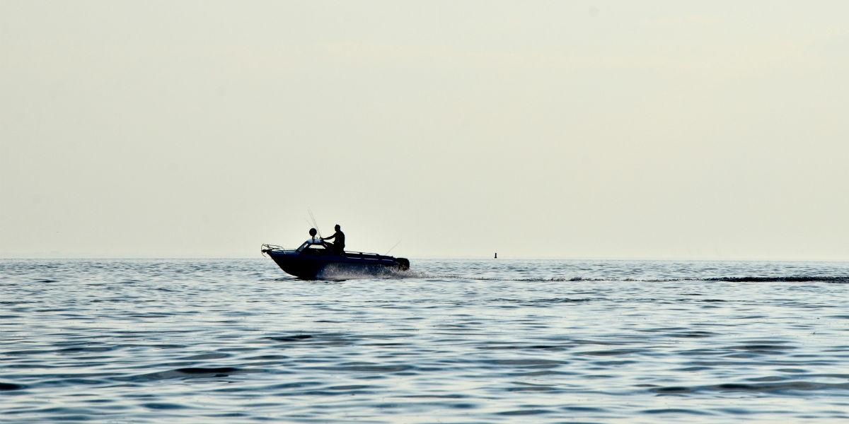 En person som kjører fort med båt et stykke unna