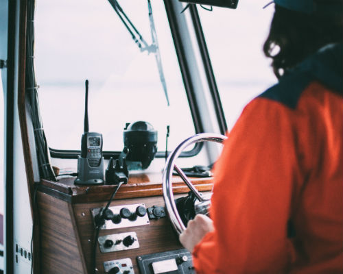 En person som står ved rattet til en mellomstor båt, sett bakfra
