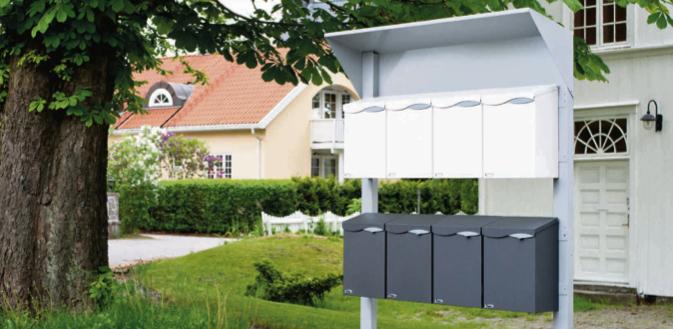 Et postkassestativ med hvite og sorte postkasser utenfor et boligfelt