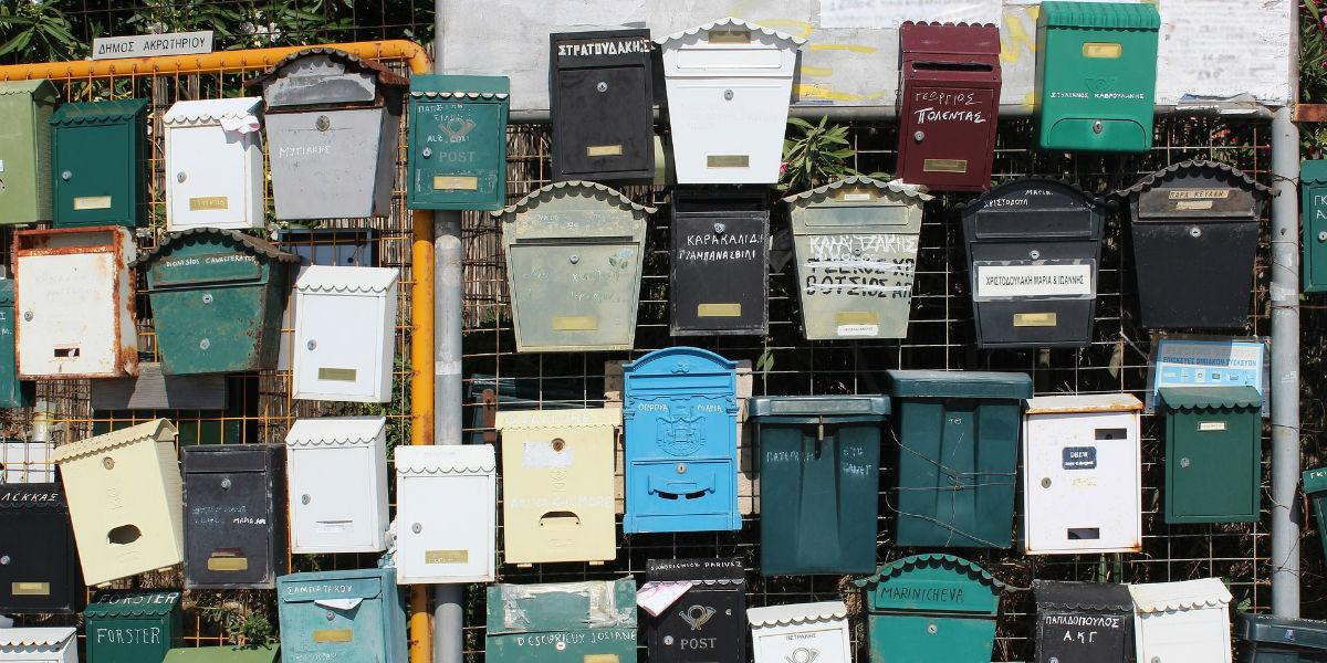 Masse ulike postkasser festet hulter til bulter på et høyt gjerde