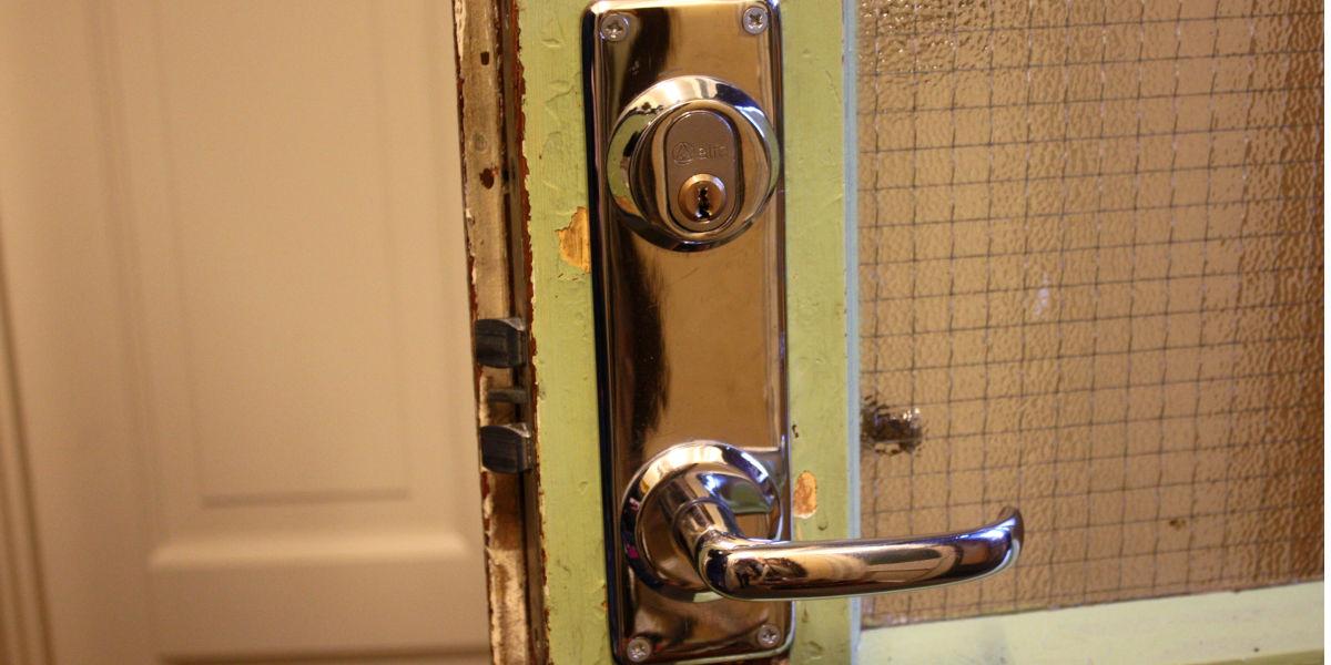 En grønn glassdør med lås og dørhåndtak